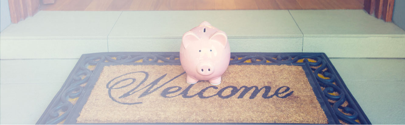 Piggy bank on welcome mat in front of open front door